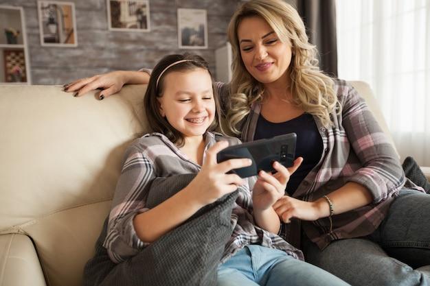 中かっこを持った小さな娘と、スマートフォンでコメディを見ながらソファに座っている母親。