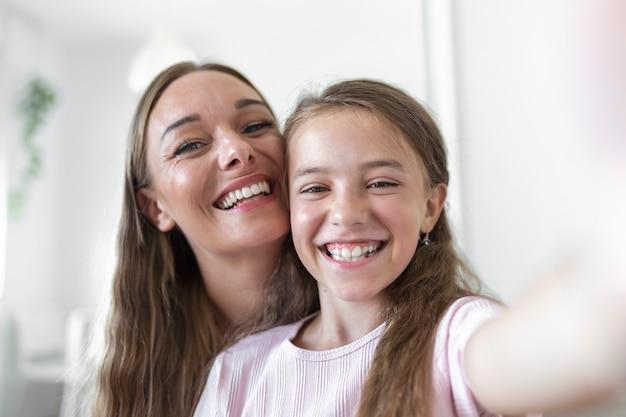 小さな娘の若い母親は、ウェブカメラのクローズアップビューに直面しています。愛らしい子供の女の子がスマートフォンを使用して、姉が自分撮り写真を撮るのを楽しんだり、vloggerが新しいvlogを記録したり、面白いアクティビティのコンセプトを楽しんだりできます