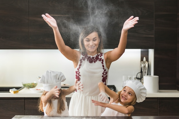 Little daughters with mother throwing flour and having fun while preparing food