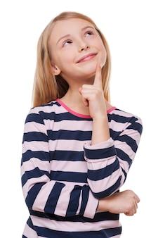 小さな空想家。あごに指を持って、白で孤立して立っている間目をそらしている陽気な少女