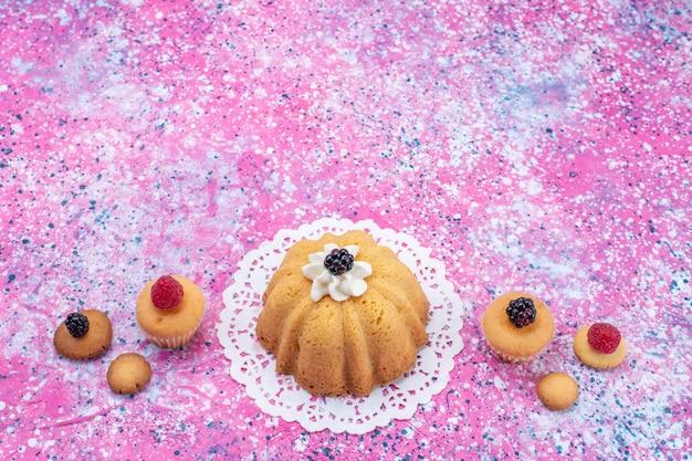 밝은 책상에 딸기와 함께 크림과 함께 작은 맛있는 케이크, 케이크 비스킷 베리 달콤한