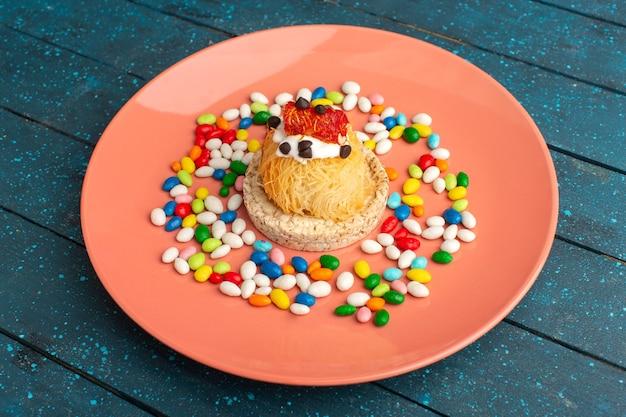Маленький вкусный торт со сливками внутри персиковой тарелки вместе с конфетами на синем