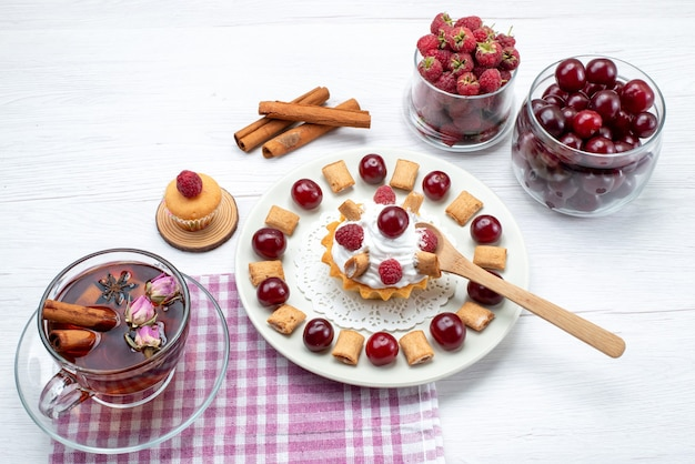Маленький вкусный торт с малиной, вишней и маленьким печеньем, чай с корицей на белом, фруктовый чай со сливками