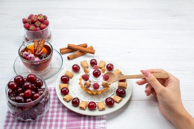 Piccola torta deliziosa con lamponi, ciliegie e piccoli biscotti, tè alla cannella sulla scrivania leggera, tè alla crema di frutti di bosco
