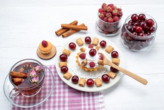 Piccola torta deliziosa con lamponi ciliegie e biscotti piccoli tè cannella su bianco, tè alla crema di frutti di bosco