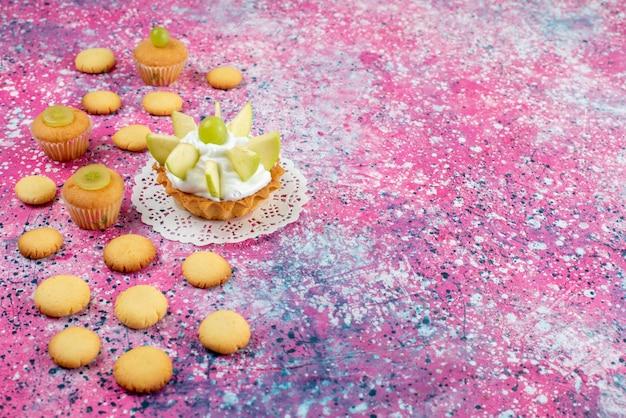 Маленький вкусный торт с нарезанными фруктами печенье на цветном, торт сладкий сахар цветной фото