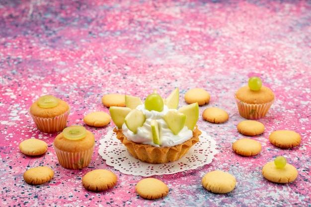 色付きの机の上にスライスしたフルーツクッキーと小さなおいしいケーキ、ケーキ甘い砂糖のカラー写真