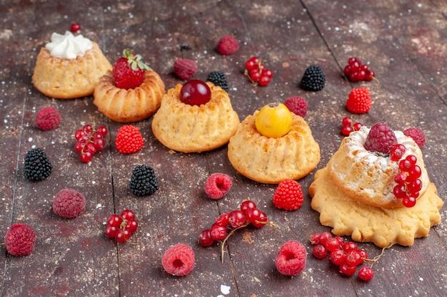 Маленькие вкусные пирожные и печенье с разными ягодами на всем протяжении коричневого деревенского, торт бисквитное ягодное печенье
