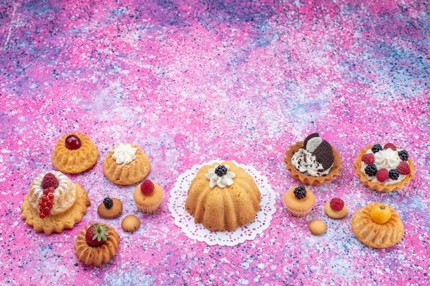 Маленькие вкусные пирожные со сливками вместе с ягодами на ярком столе, торт бисквитно-ягодный сладкий