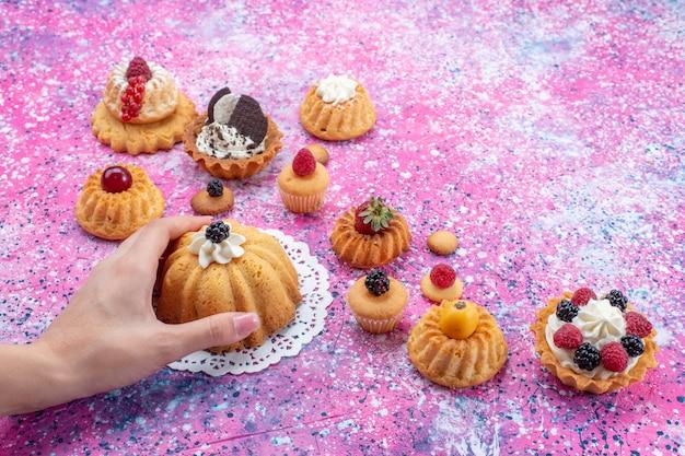 Piccole deliziose torte con crema insieme a diversi frutti di bosco sulla scrivania luminosa, torta biscotto bacca dolce cuocere