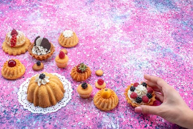 Piccole deliziose torte con panna insieme a diversi frutti di bosco su una torta dolce ai frutti di bosco