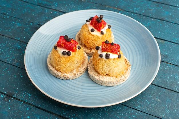 Маленькие вкусные пирожные со сливками и мармеладом сверху внутри синей тарелки на синем