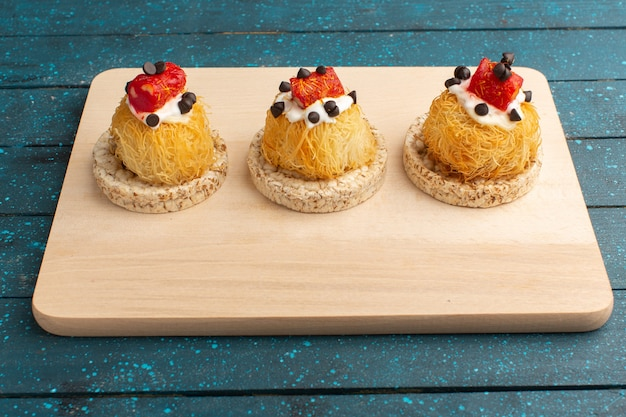 Little delicious cakes with cream and marmalade on top on wooden desk and blue
