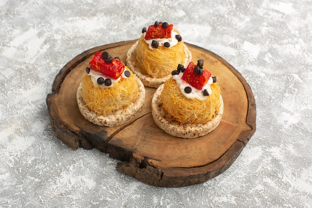 Little delicious cakes with fruits on brown wooden desk