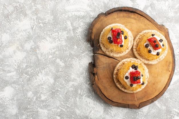 Маленькие вкусные пирожные с фруктами на коричневом деревянном столе