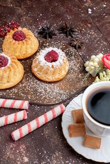 Маленькие вкусные пирожные с малиной вместе с леденцами в стиках, кофе на деревянном столе, торт, сладкие фрукты, выпечка, бисквит, ягода
