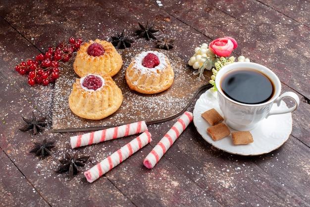 ラズベリーとクランベリーの小さなおいしいケーキと木製の机の上のスティックキャンディーコーヒー、ケーキ甘いフルーツはビスケットベリーを焼く