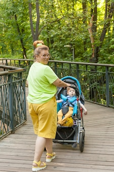 A little disabled boy in a wheelchair with his mother in a city park on a summer day. infantile paralysis. disability. inclusivity. restriction of movement.