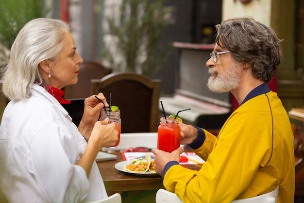 약간의 불일치. 점심 시간에 카페 테이블에 앉아 힘든 이야기를 하고 있는 실망한 부부.