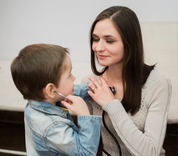 청진기를 사용하여 그녀의 가슴을 듣고 그의 어머니와 함께 노는 작은 의사 소년