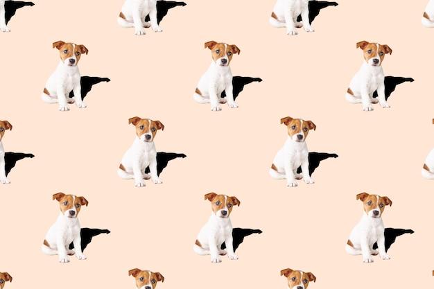 ピンクの背景に小さな犬。ジャックラッセルテリアの子犬犬。シームレスパターン