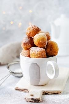 リトルドーナツ。ヴィンテージのセラミックカップに粉砂糖をまぶして揚げた自家製カッテージチーズクッキー