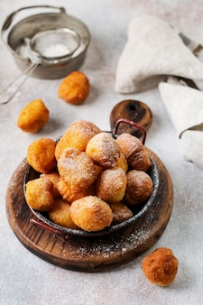 Маленькие пончики. домашнее творожное жареное печенье во фритюре и посыпанное сахарной пудрой на винтажной тарелке
