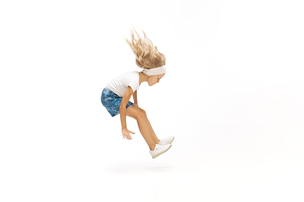 Little and emotional caucasian girl jumping and running isolated on white