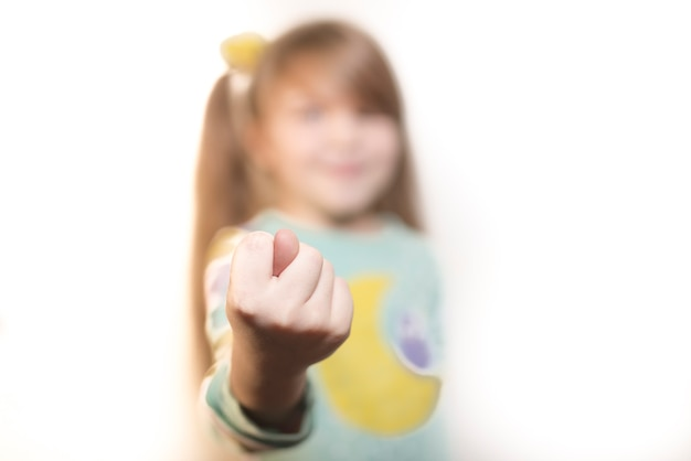 Little emotional girl shows gesture fig isolated on white background