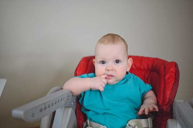 작은 감정적 인 갓난 재미있는 유아 소년은 높은 의자 아기 얼굴 표정을 먹이에 앉아