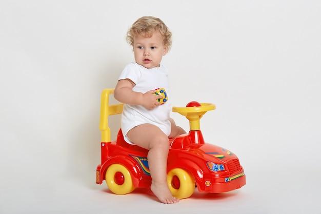 裸足でトロカーに乗っている小さなヨーロッパの少年、白いスーツを着て、目をそらしている巻き毛の金髪の幼児