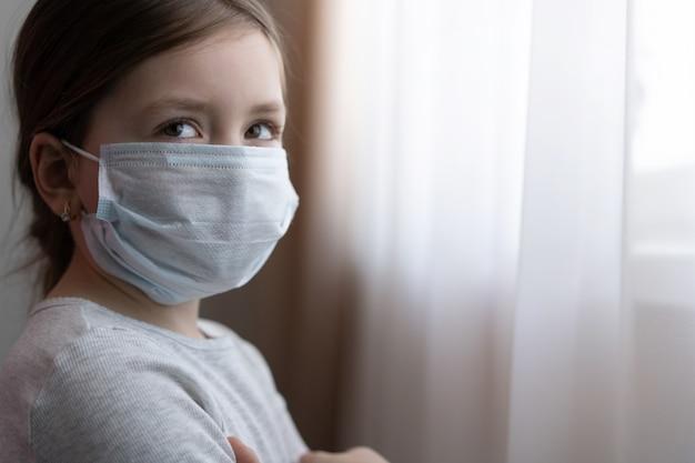 Маленькая европейская девочка в маске для защиты covid-19. больной ребенок маленькие девочки смотрят в окно. копировать пространство
