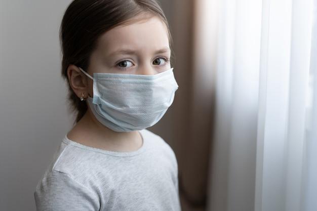 Covid-19を保護するためのマスクを身に着けている小さなヨーロッパの女の子。病気の子供小さな女の子が窓を見る。コピースペース