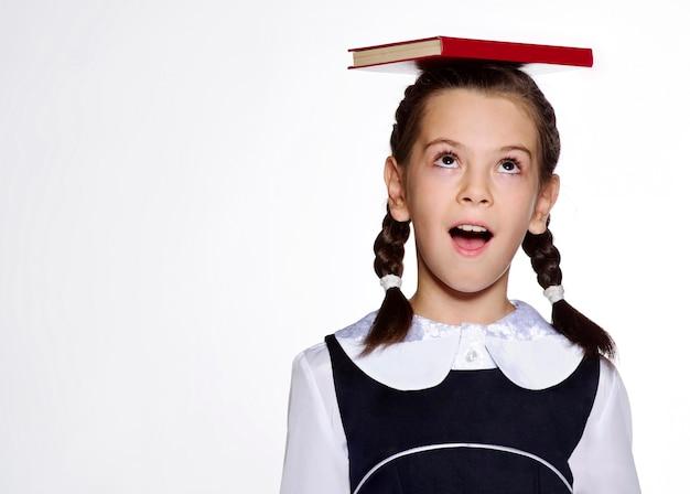 Little european school girl student posing in studio