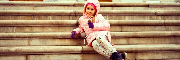 Маленькая европейская улыбающаяся шестилетняя девочка в осенней одежде сидит на ступеньках усадьбы в осеннем парке. знамя