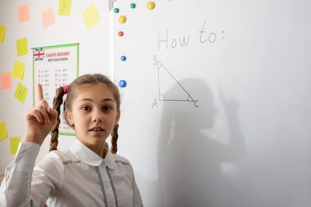 Маленькая взволнованная девочка показывает пальцем вверх и готова сказать правильный ответ на упражнение