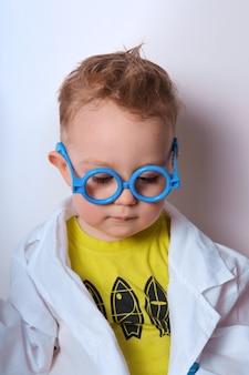 小さな探検家の少年は科学者を演じる青い眼鏡をかけた面白い子供かわいいカラフルな写真医者