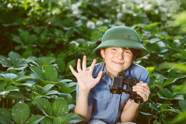 Маленький исследователь с биноклем в лесу