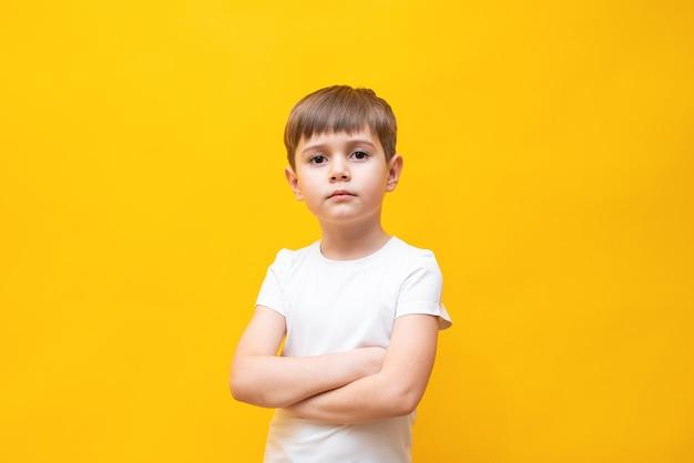 スタイリッシュな白いポロシャツを着た5〜6歳の金髪の茶色い目の小さな男の子、腕を胸に折りたたんで、黄色の壁に隔離