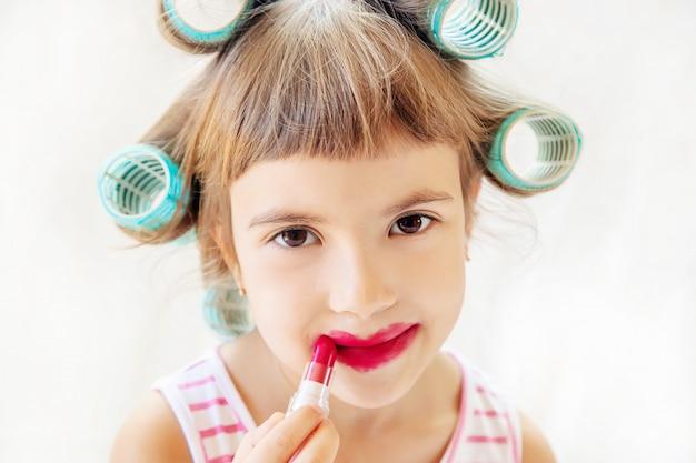 작은 패션 소녀. 소녀는 그녀가 화장하고 매니큐어를합니다. 선택적 초점.