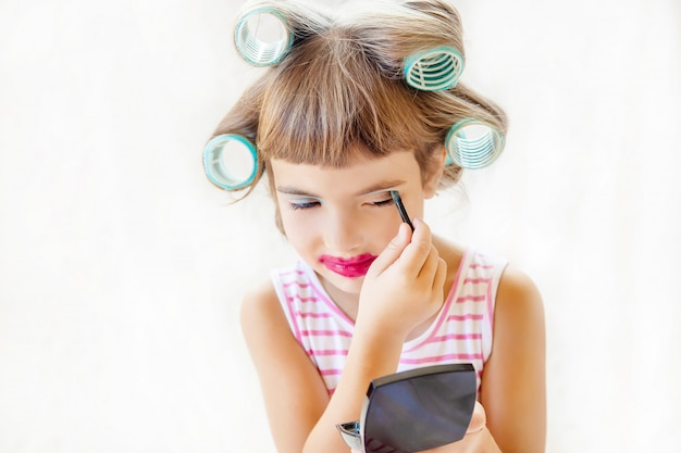 Little fashion-girl. girl does her make up and manicure. selective focus.