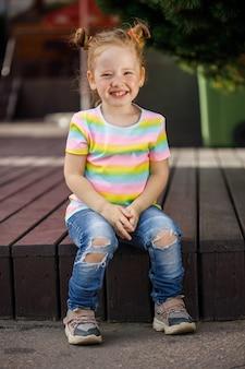 Маленькая модная девочка в джинсах и цветной футболке