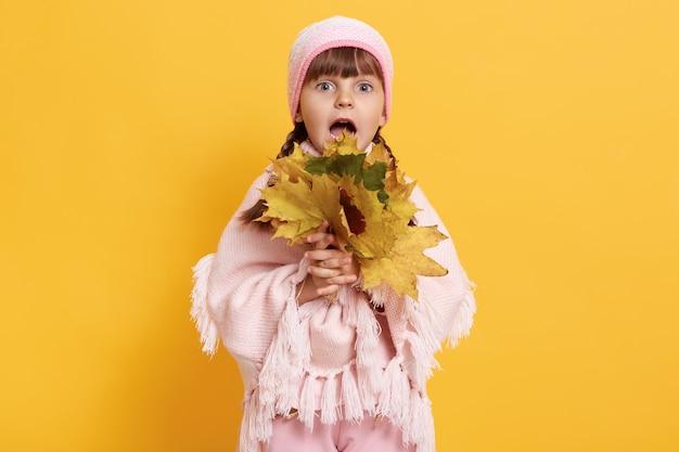 Маленькая модная девочка в теплой одежде держит букет осенних листьев