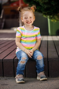 Little fashionable girl in jeans and a colored t-shirt
