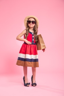 Little fashionista with a shopping bag in a summer hat and glasses , on a colored pink background in mom's shoes , the concept of children's fashion
