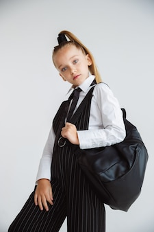 흰색 바탕에 배낭 학교 유니폼 포즈 작은 여성 백인 모델.