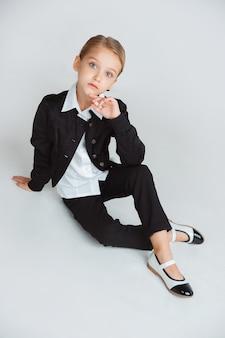 Piccolo modello caucasico femminile che posa in uniforme scolastica su priorità bassa bianca.