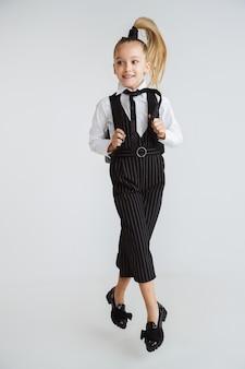 Piccolo modello caucasico femminile che posa nell'uniforme della scuola con lo zaino su priorità bassa bianca.