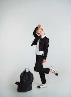 Little female caucasian model posing in school's uniform with backpack on white background.