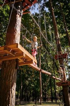 ロープパーク、遊び場での小さな女性登山家のレジャー。吊橋に登る子供、休暇での極端なスポーツアドベンチャー、屋外でのエンターテイメント